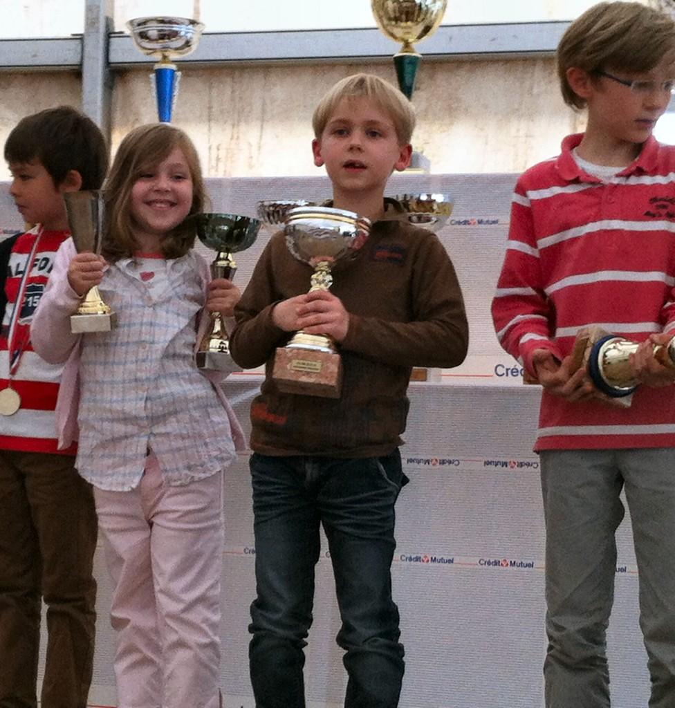 Sur la photo Emma Schmidt avec ses 2 coupes : 1ère petite poussine et plus jeune joueuse du tournoi (née en avril 2007). A droite Pierre-Matthieu Prat.